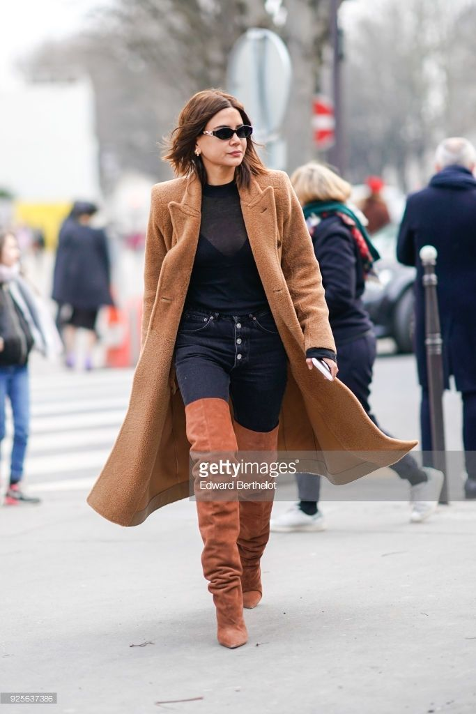 Christine Centenera wears a brown coat, a black mesh top, black pants, brown