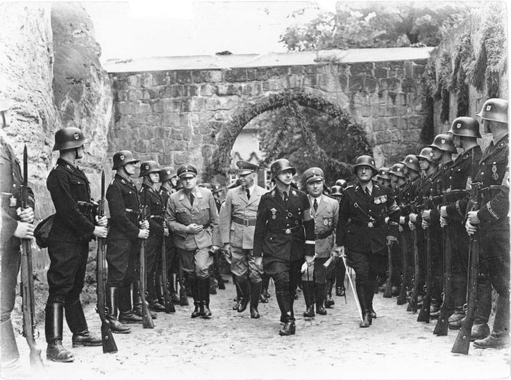 "This photo was taken on Cathedral Hill in Quedlinburg, Harz mountains in the west of Saxony-Anhalt, Germany. It shows Heinrich Himmler on the way to the grave of the German King Henry I. Behind him, from left, Hans Frank, Wilhelm Frick and Robert Ley. Himmler had ordered excavations on Cathedral Hill of Quedlinburg in search of ""Aryan proof"" in German ancestry. He also saw himself as the reincarnation of King Henry I (AD 876 - 936)."
