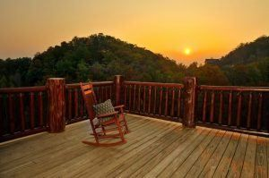 A rocking chair on the deck of a large group cabin in Gatlinburg TN with mountain views.