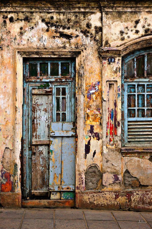Porta e janela em Catende, estado de Pernambuco, Brasil. Sob a pintura descascando, bonitos toques de cor brilhante.