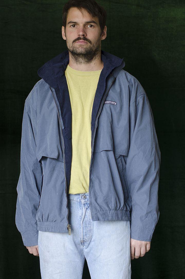 Chaqueta largo medio, cuello alto, bolsillos frontales, cremallera y botones frontales aplique frontal, color plata escarchado, puños con botón, color gris azulado.