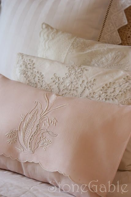 Tiny lace pillows on a bed..love.