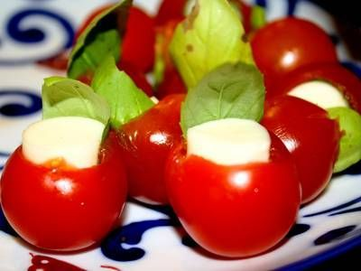 These cute and colorful appetizers are quick and easy to make, using cherry tomatoes stuffed with basil-wrapped mozzarella.