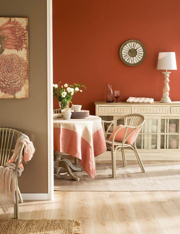 Comedor con pared color teja y marrón, aparador en crema con puertas de cristal, reloj, lámpara de sobremesa y mesa redonda de comedor con silla