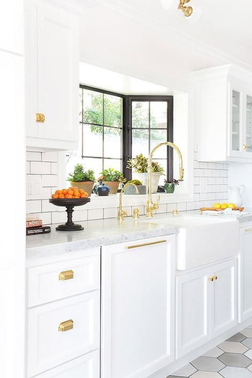 White and gold kitchen features white cabinets adorned with antique brass cup pulls paired with carrera countertops and a white subway tiled backsplash accented with dark grout.