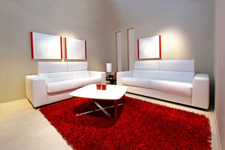 Minimalist living room with grey walls, 2 white sofas and large red rug