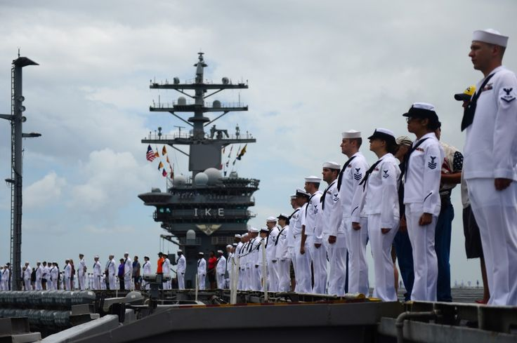 Sailors man the rails on the flight deck of the aircraft carrier USS Dwight D. Eisenhower (CVN 69) as the ship arrives at Naval Station Norfolk