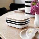Omaggio-smørboks sort/hvid-stribet på træbord med stempelkande i baggrund