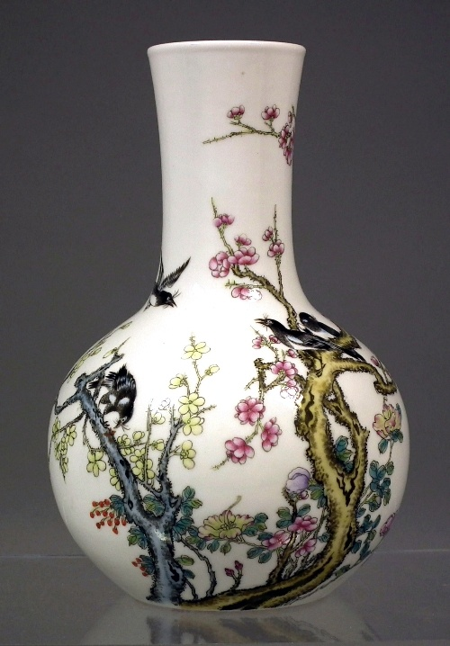 "An early 20th Century Chinese porcelain bottle shaped vase decorated in the ""Famille Rose"" palette with magpies and prunus blossom, 7.5ins (190mm) high"