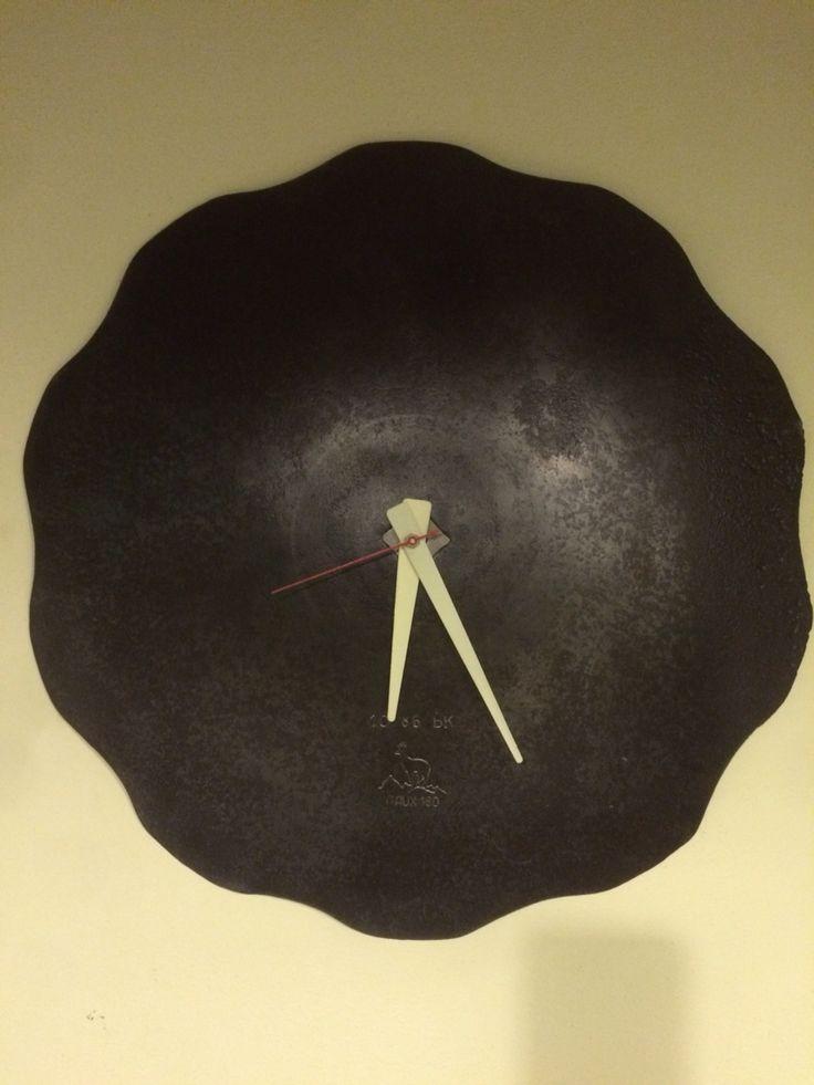 Orologio a parete ricavato da una ruota in ferro di attrezzo agricolo.