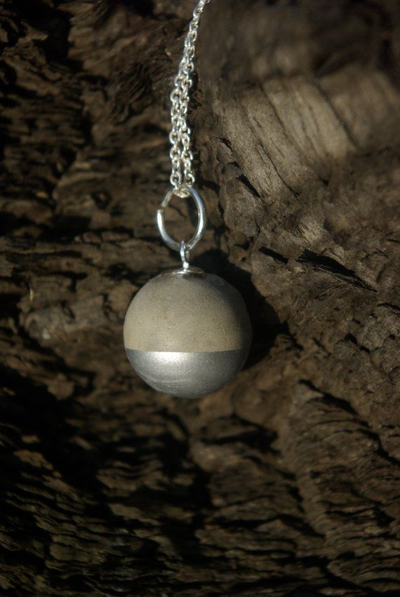This unique necklace consists of a sterling silver chain, with a concrete sphere pendant, which has been partly dipped in silver enamel. Normally
