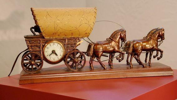 Kutschenuhr von United Clock Company aus den USA:(Covered Wagon) Die Firma produzierte 10 Jahre bis 1960)wurde berühmt für ihre Uhren, die als Preise im New Yorker Karneval verliehen wurden. Der Planwagen ist eine Leuchte, die Peitsche würde sich bewegen, aber die Stromversorgung ist bei der Uhr 110 Volt stillgelegt. - Carneval Clock  Wert 200 €