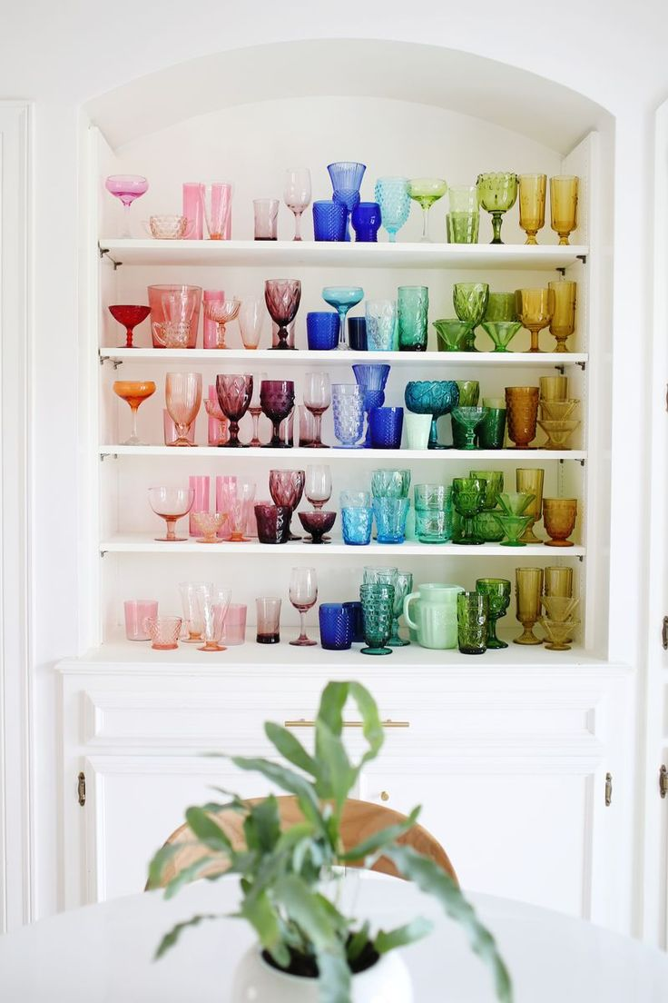 The colored glass collection of Ellie Larson (of A Beautiful Mess) stands out in her all-white breakfast nook.