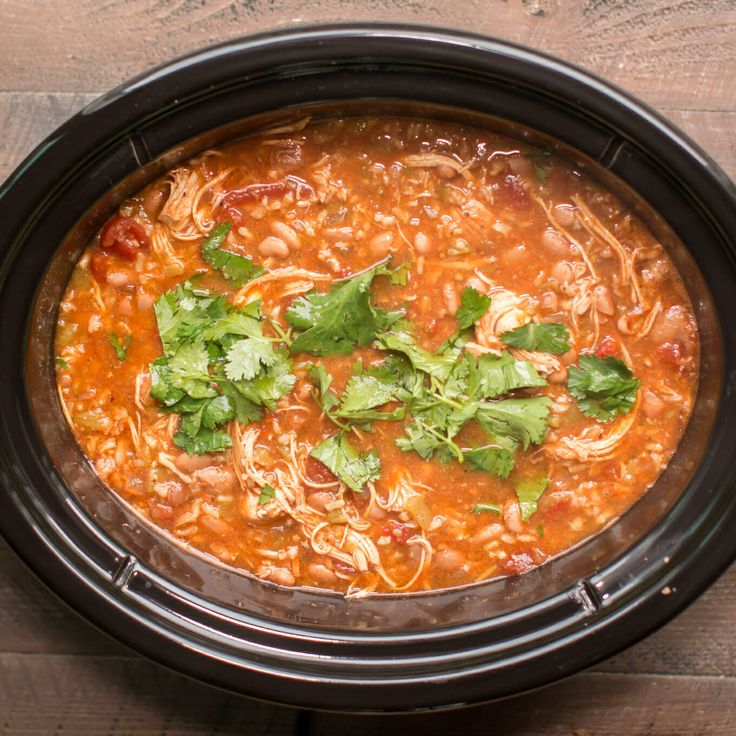 Slow Cooker Mexican Chicken soup is filled with beans and brown rice and is flavored with spices and enchilada sauce.