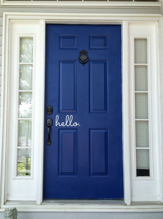 After fixing the damage, Kate painted the patched-up door a bright navy blue and replaced the old brass hardware with a set in bronze finish. She and Adam decided to keep the original door knocker because it had character but spray-painted it to match the new metallic hardware. The cherry on top was a decal next to the door handle to welcome visitors with a friendly hello.
