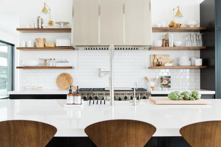 White and black kitchen features a black cabinets adorned with brass hardware paired with Pure White Quartz countertops and a white mini subway tile backsplash.