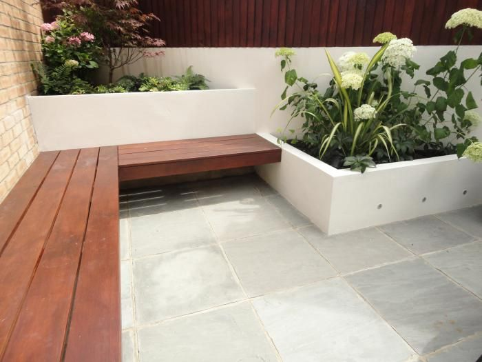 Kandla Grey Sandstone is a consistently coloured grey sandstone that looks equally good in contemporary and traditional design settings.  Here its been laid in a contemporary city garden featuring hardwood seating and rendered planters