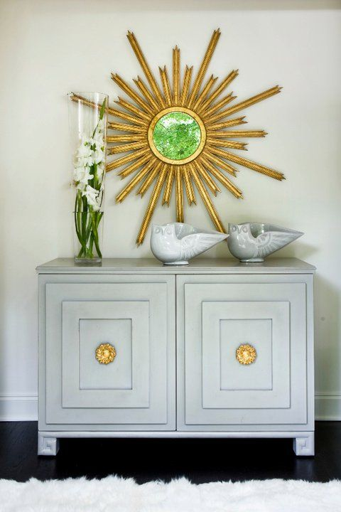 Beautiful vignette with flat panel chest painted a light gray with gold hardware, gold sunburst mirror and gray owl bowls.