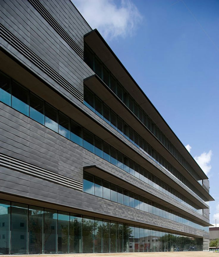 """""""The envelope design is based on the time-honoured quality of zinc and the relation (by opposition) to the context: zero expressivity in the surfaces and a marked chiaroscuro effect in the projections that protect the windows facing the sun."""" Office Building for the World Trade Center Almeda Park, Cornellà (Barcelona)."""