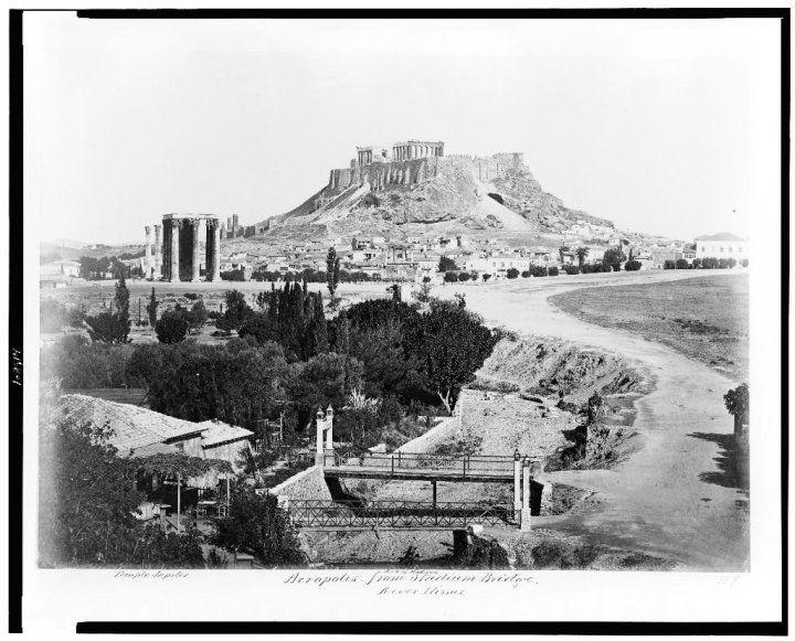 Η περιοχή του Ολυμπιείου, φωτογραφημένη από τους πρόποδες του Αρδηττού. Σε πρώτο πλάνο ο Ιλισσός –χωρίς καθόλου νερό- και οι δυο μικρές γεφυρούλες που για δεκαετίες ένωναν την πλευρά του Ζαππείου με αυτήν του Βατραχονησιού, ενός είδους «νησίδας» που δημιουργείτο από τη ροή του Ιλισσού μετά το Παναθηναϊκό Στάδιο, στο χώρο όπου σήμερα απλώνεται ο στίβος του Εθνικού Γυμναστικού Συλλόγου.
