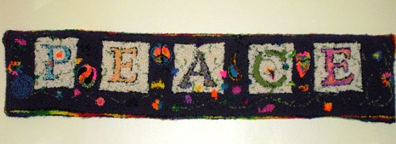Plush wall hanging that proclaims Peace. Delicate floral tendrils weave around the letters. Created using the hand technique of rug punching with yarn, rather than the wool strips of rug hooking.