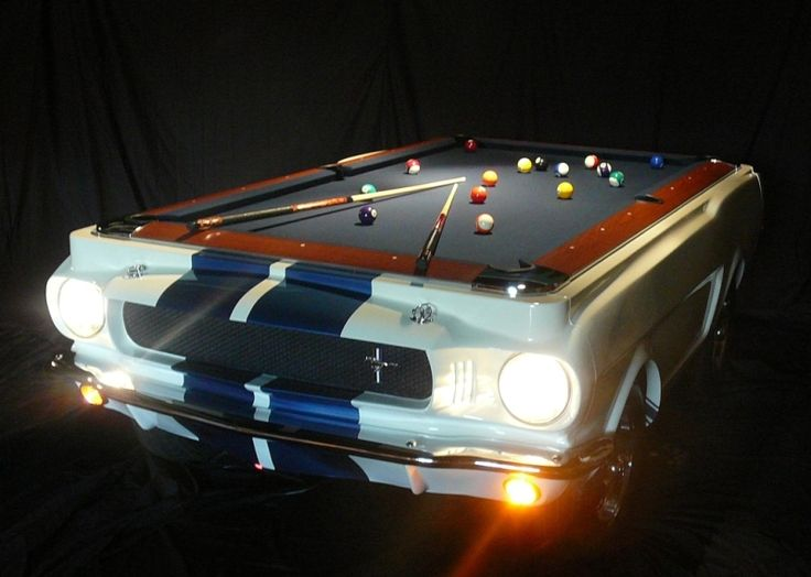 The table is regulation size, and molded to a real 1965 Shelby GT350 (by which we hope they mean a continuation Shelby and not an original) complete with chrome bumpers, and authentic badging, and working lights.