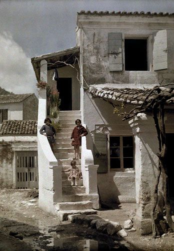 Girls stand on a stairway of a house in a Greek fishing village, Benizze, Corfu; 1920's