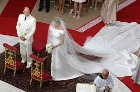 Mónaco 02 de julio 2011 la Princesa Charlene y su vestido por Georgio Armani. El vestido estaba hecho de satén de seda y organza de seda, y tenía 40.000 cristales, 30.000 madre perlas, y 30.000 piedras de oro. El vestido tenía dos colas, una extraíble ya que era de aproximadamente 20 pies de largo, y otra más corta que fue de aproximadamente diez pies de largo. Charlene llevaba un velo de tul de seda y un adorno para el pelo de brillantes.
