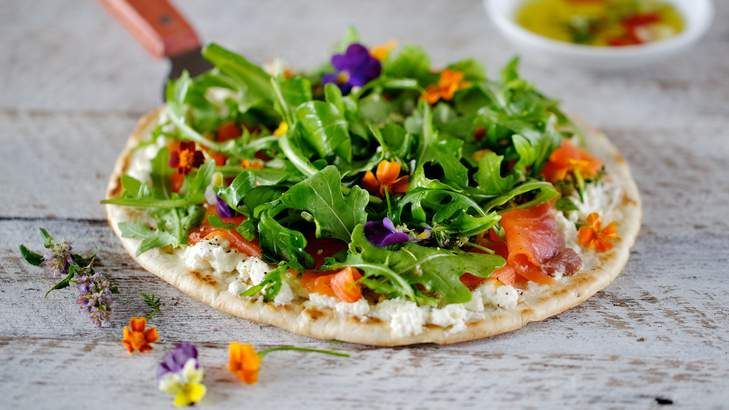 Pizza plus salad equals salad pizza! Top pizza bases with ricotta, smoked salmon, rocket and edible flowers - easy!