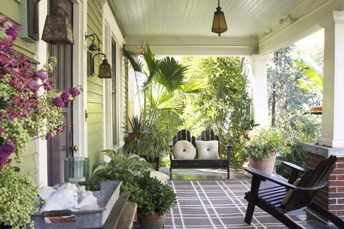 Green wooded walls with abundance of potted plants. Teamed with dark wooden chairs.