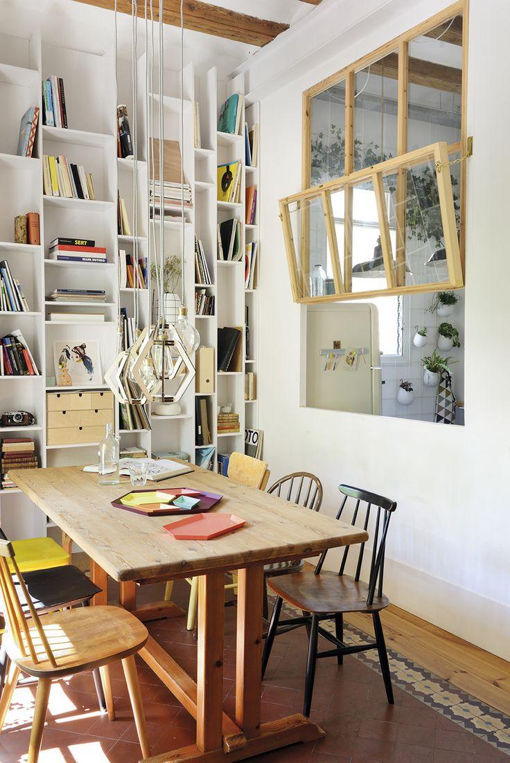00436844. Office con una gran estantería en al pared y diferentes estilos de sillas separada de la cocina por unas pequeñas ventanas_00436844