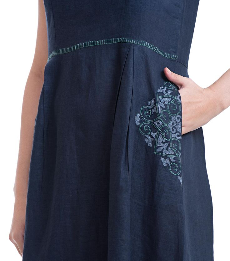 Linen Dress Round neck, sleeveless long dress Box pleat detailing on the front Stitch detailing at the neck line and waist line Placement embroidery on the side pockets and back yoke Button detailing at the back ...