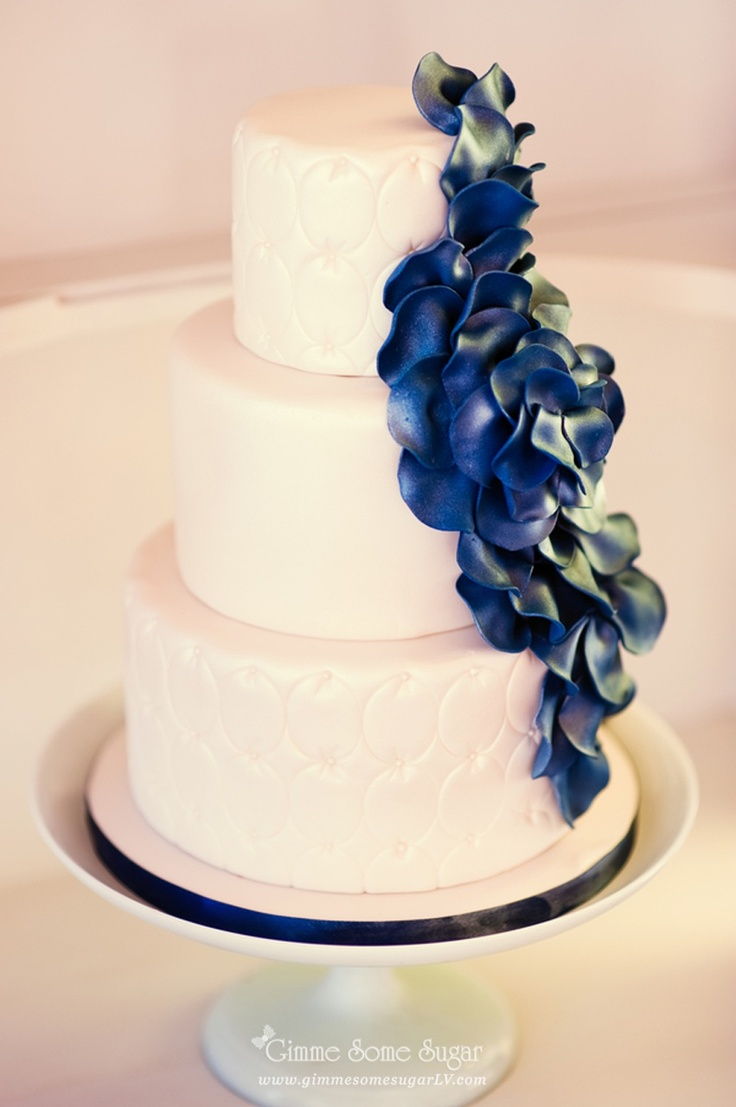 Beautiful Yet Simplistic White Cake With Blue Flower Petals Cascading Down 1 Side