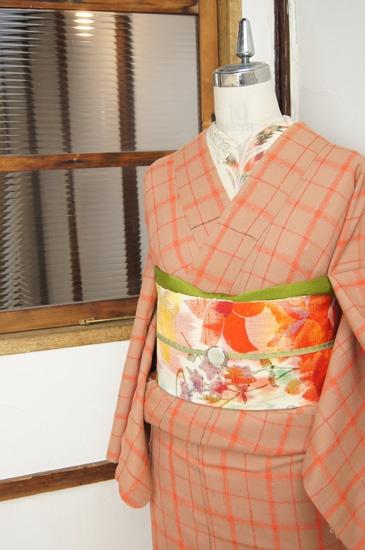 蜂蜜色がかった優しいベージュと、綺麗なコーラルオレンジで織り出された大胆チェックに心はずむウールの単着物です。