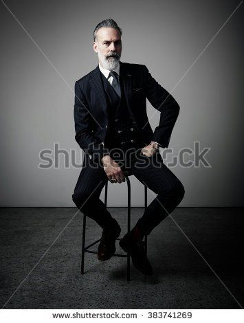 Portrait of adult businessman wearing trendy suit and sitting studio on chair against the empty wall. Vertical