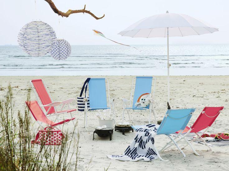 Sandstrand med vikbara strandstolar och vilstolar i ljusblått och ljusrött. Dessutom ett vitt parasoll och två små kolgrillar.