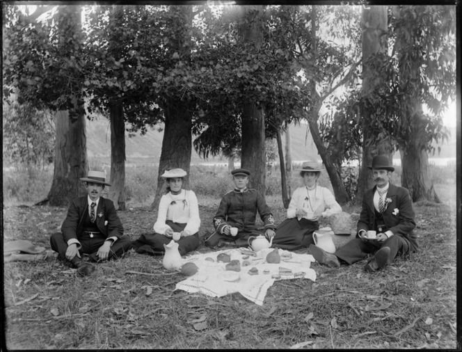 Group of unidentified young men and women with hats, one man in uniform, having a picnic in front of tall trees, with a bay and steep hills beyond, probably Christchurch region c1910