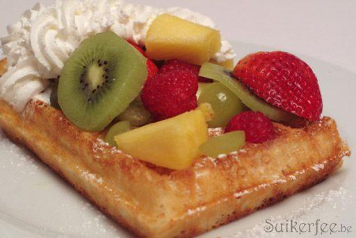 Verse brusselse wafel met bloemsuiker, slagroom, aardbeien, ananas, druiven, frambozen, kiwi en appel.