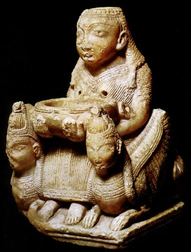 The Canaanite goddess is also shownseated between lions,  which are now winged cherubim with lion's bodies and women's heads.  Phoenicians brought this deity to southwestern Iberia.  She is an alabaster ritual vessel; when libation is poured into her,  the liquid shoots out from her breasts into the basin she holds.  Tutugi, Spain, 7th century.