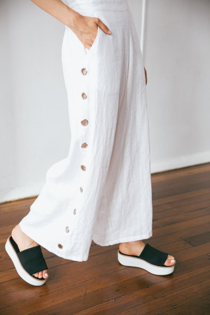 OVERSIZED WIDE LEG JUMPSUIT.  THICK ADJUSTABLE STRAPS. (Button adjustable at back) FRONT BIB FEATURES SINGLE EYELET DETAIL.  OUTSIDE LEG FEATURES EYELET DETAIL FROM POCKET TO HEM.  WHITE.  100% LINEN.  MODEL WEARS SIZE 8. (Would fit size 10) MODEL IS 175CM TALL.