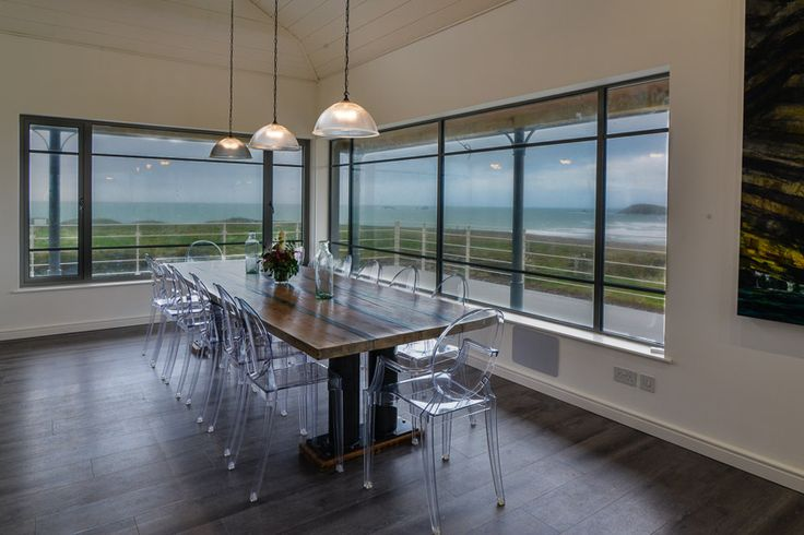 Trenouth - Cornwall.  A Cornish, self catering beach holiday house to rent at Treyarnon Bay, just a short drive from Padstow.  Such a clever simple interior style.  The three lights and great use of the ghost chair enhance this amazing back drop.