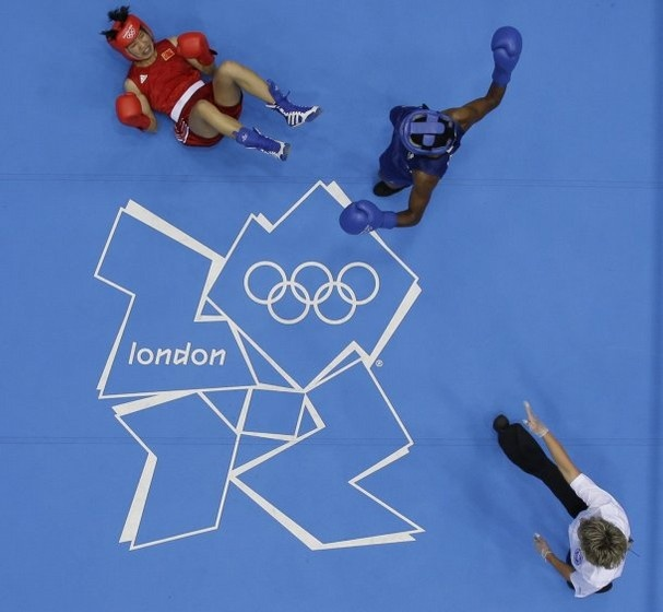 China's Ren Cancan, is knocked down by Great Britain's Nicola Adams, blue, during their women's final flyweight 51-kg boxing match at the 2012 Summer Olympics, Thursday, Aug. 9, 2012, in London. (AP Photo/Hassan Ammar)