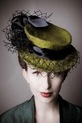 Moss green hat with solid crown, black ribbon, and netting over the brim