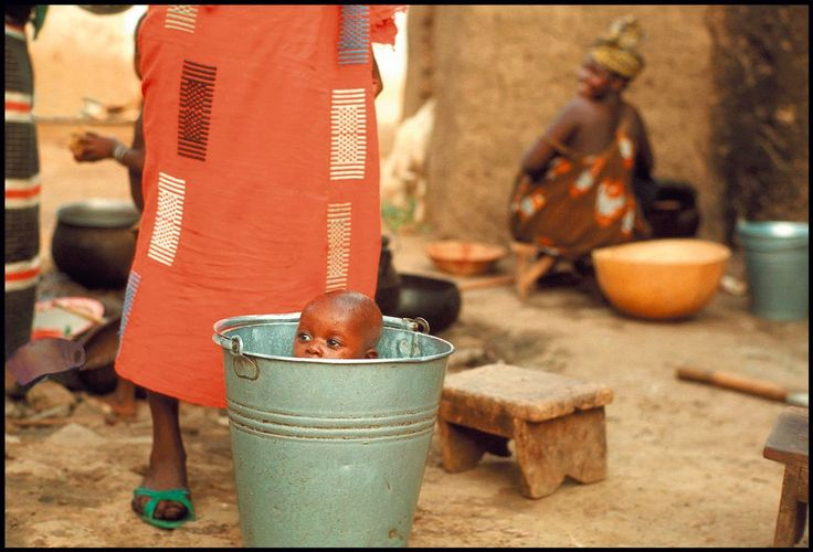MALI. Bamako. Child gets washed in a bucket at outdoor standpipe. 1970.