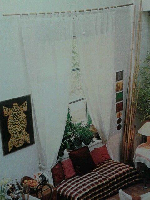 Due teli di mussola bianca, Sono fissati con asole passanti ad un semplice bastoni di bambù. Due embrasse intrecciate sempre di mussola trattengono le tende sui lati lasciando libero il davanzale per ospitare tante piante verdi