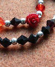 RED ROSES AND BLACK VELVET: Par de pulseras en piedras negras y rojas, herrajes plateados y detalle en rosa roja resina.