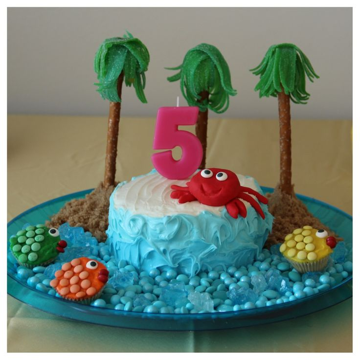 She requested a crab birthday cake and here it is!  How to Host a Caribbean Party in 10 Easy Steps. Globetrotting Mommy, Under the Sea, Caribbean, party decor, birthday, kids parties, tropical party ideas, birthday, party decor, birthday cake, under the sea party, crab birthday cake, blue candy ocean, pretzel and candy palm trees, fish cupcakes.
