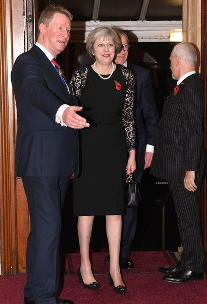 British Prime Minister Theresa May and her husband Philip (behind) attend the annual Royal Festival of Remembrance at the Royal Albert Hall on November 12, 2016 in London, England.
