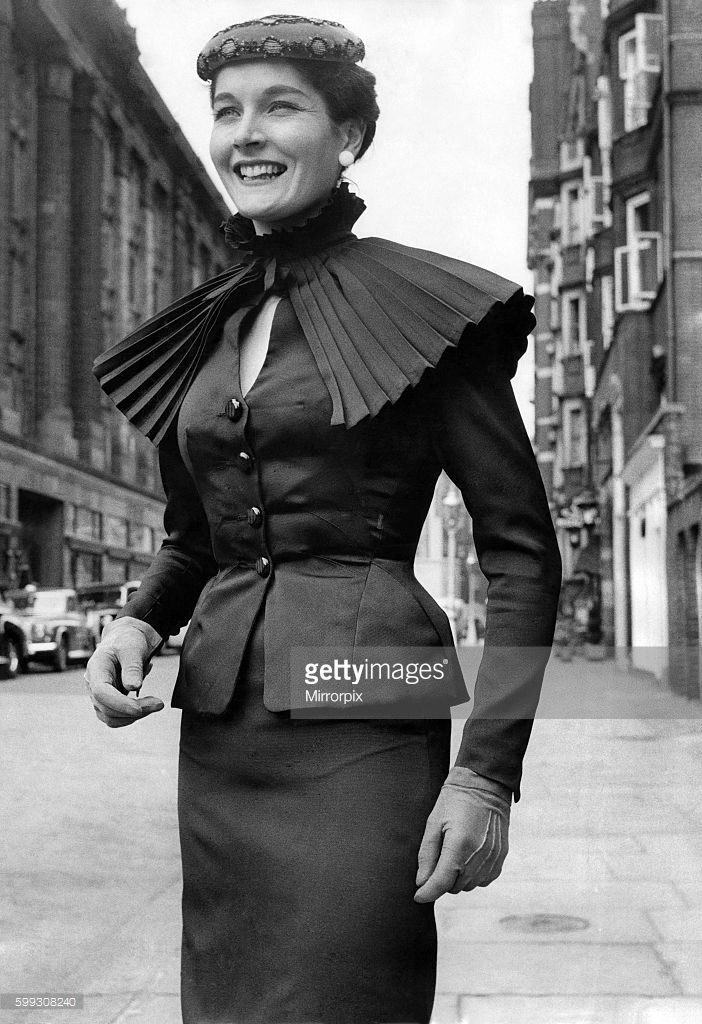 A black pure silk suit with small pleated detachable ruff cape of mushroom shape. August 1955 P021268