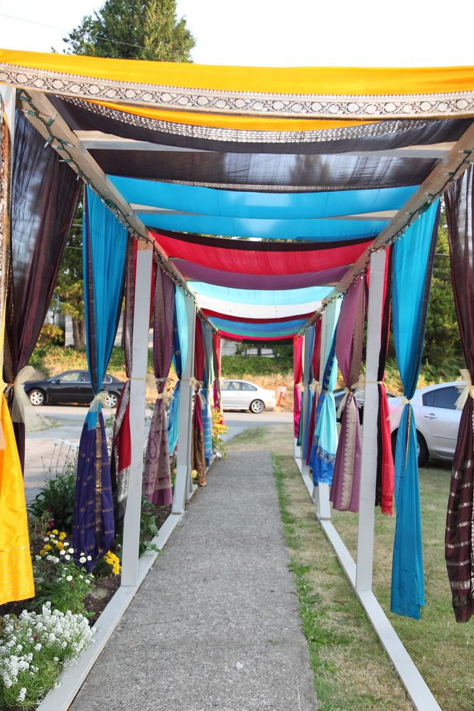 Indian wedding - outdoor walkway at wedding house decorated using old sari's and outdoor lights.